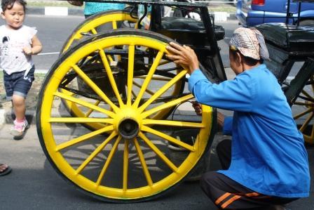 Kusir delman sedang membetulkan roda delmannya
